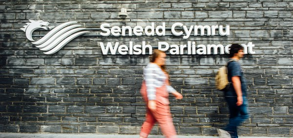People walking past the Senedd signage